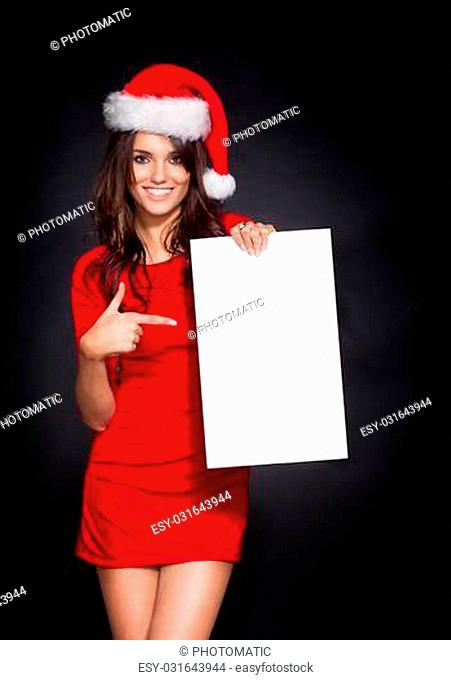 Traditional woman Christmas Santa holding a blank sign, showing something by her index finger