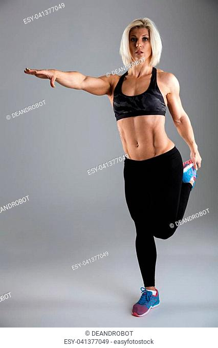 Full length portrait of a muscular adult sportswoman standing and stretching her leg isolated over gray background