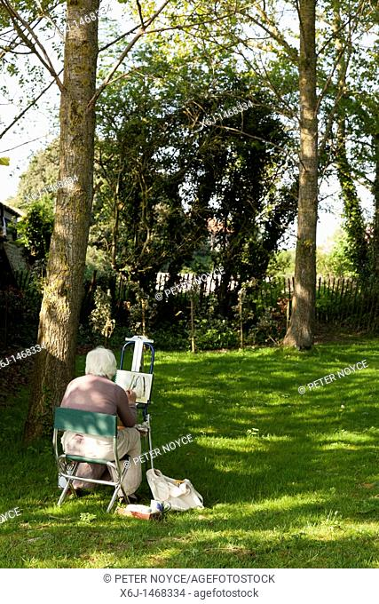 artist on stool painting under some trees on a sunny day