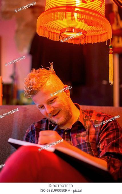 Man sketching under orange lamp