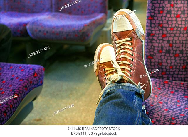 Feet of a man leaning on the seat of a train. England, UK, Europe
