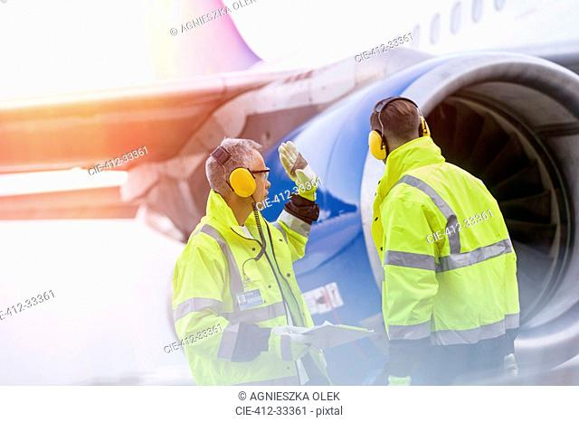 Airport ground crew workers talking near airplane