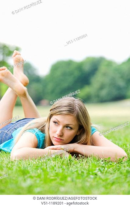 Portrait of a pensive woman lying down in park
