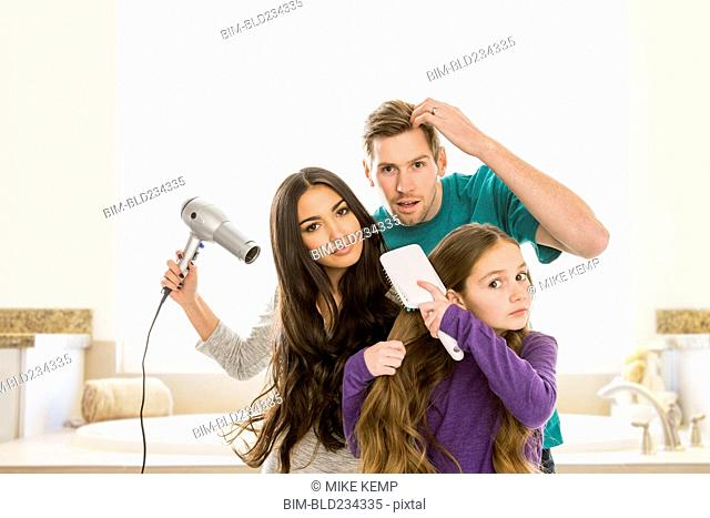 Family grooming hair in bathroom
