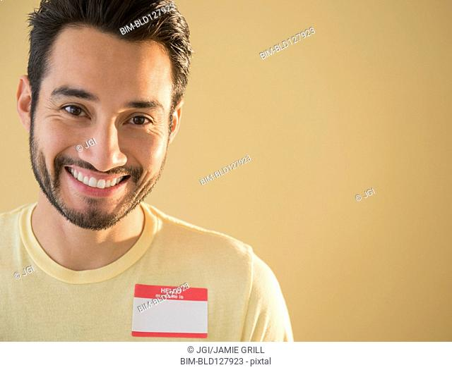 Mixed race man wearing name tag