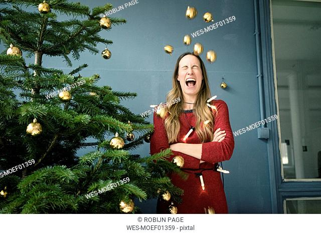Screaming woman standing besides Christmas tree