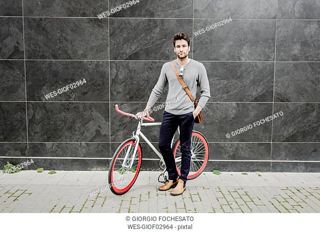 Portrait of young man with his racing cycle