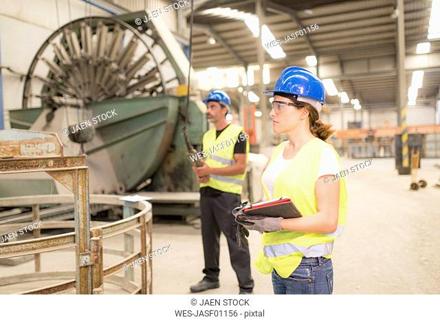 Woman standing in factory hall with man using control