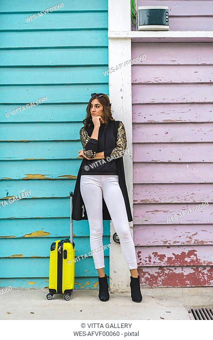 Young woman with yellow trolley bag waiting in front of wooden facade