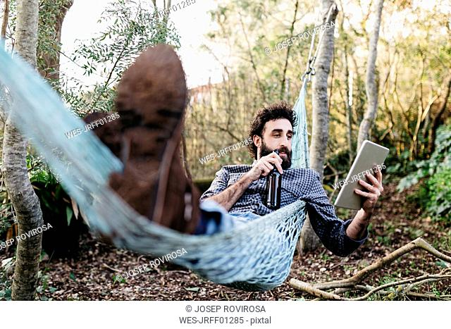 Man lying in hammock drinking beer and using tablet