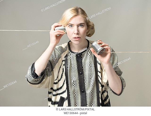Blonde woman using tin can phone. Conceptual image of connection and communication