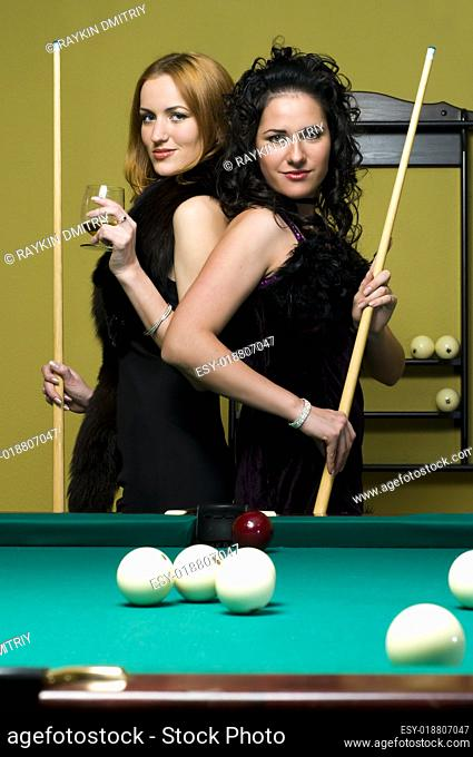 Two girls are playing billiards