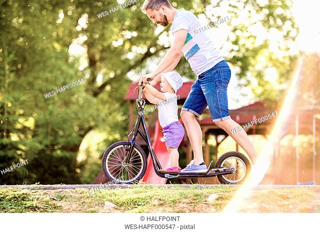 Father and little daughter together on a scooter