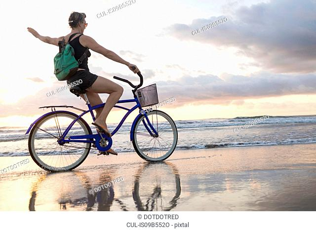Woman waving while cycling on beach at sunset, Nosara, Guanacaste Province, Costa Rica
