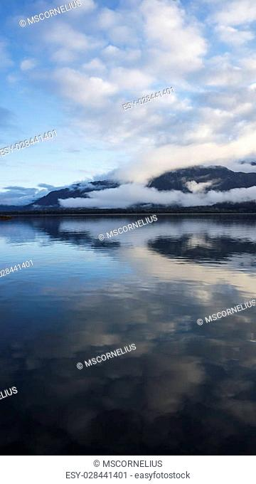 Still water in Southeast Alaska with cloud reflections at sunset