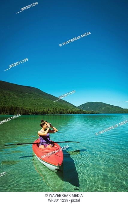 Woman looking through binoculars while sitting in kayaking