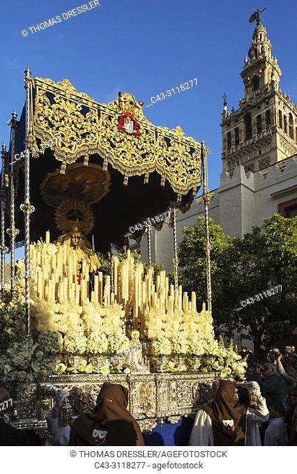 Penitents and lavishly decorated float with the Blessed Virgin at the Semana Santa (Holy Week) of Seville. Top right the Moorish Giralda