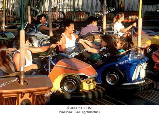 Latino family on the bumper cars at Santa Monica Pier, California