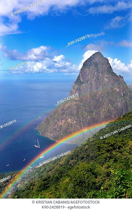 Vista of the granite cone of Petit Piton and the Caribbean Sea with blue sky, clouds and an huge rainbow spanning across the image, St Lucia, Windward Islands