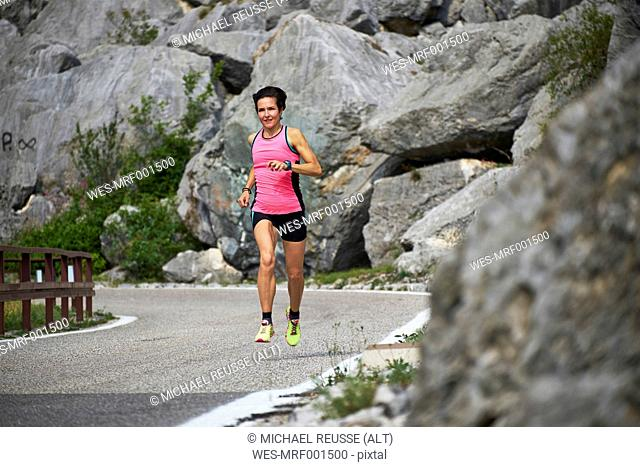 Italy, Trentino, woman running on road near Lake Garda