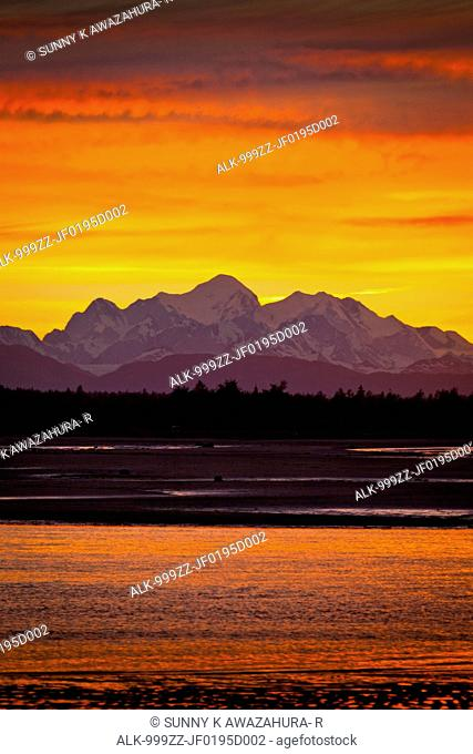 Colorful red and orage sunset behind the Fairweather Mountains with Salmon River delta in the foreground, Glacier Bay National Park & Preserve, Southeast Alaska