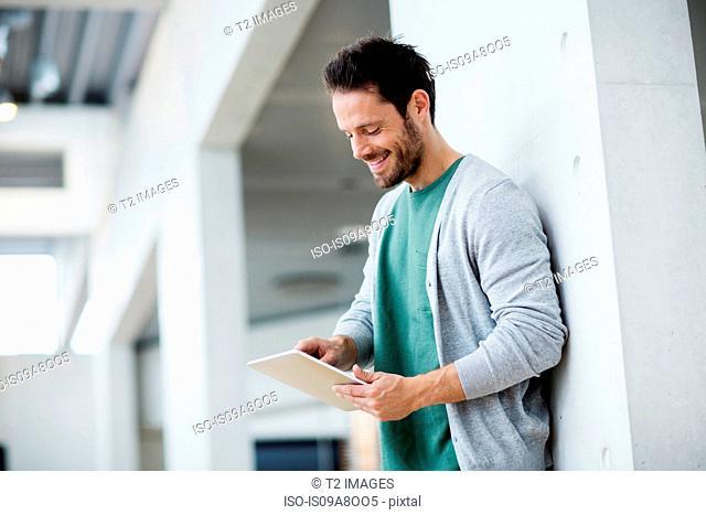 Man looking down at digital tablet