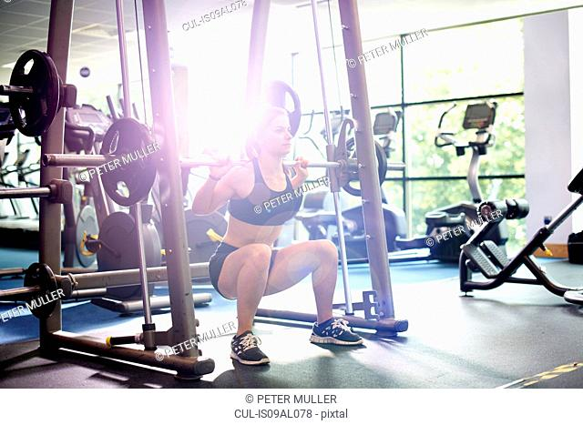 Young woman weight lifting with barbell
