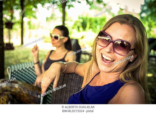 Caucasian women sitting in chairs in backyard