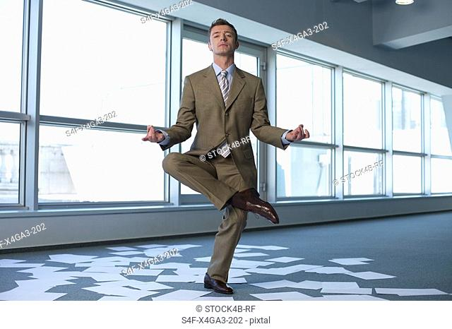 Meditating businessman in an empty office, sheets of paper on floor