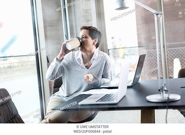 Businesswoman in office drinking coffee