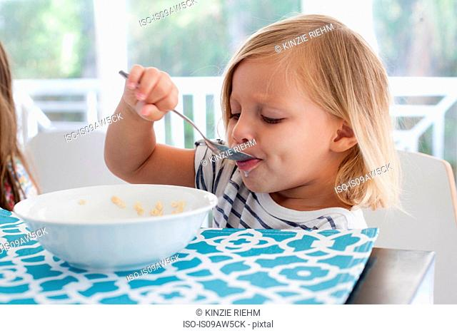 Girl eating breakfast from bowl with spoon