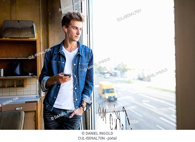 Young man listening to earphones and gazing through cafe window
