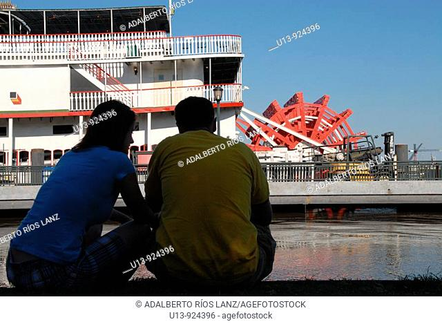 Couple observing the Natchez steamboat on the Mississippi riverside, New Orleans, Louisiana, United States