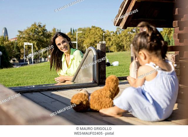Smiling mother with daughter on a playground