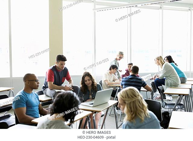 Professor and college students studying in groups classroom