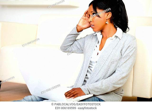 Portrait of a stressed young black woman working on laptop while is sitting on the floor at home indoor