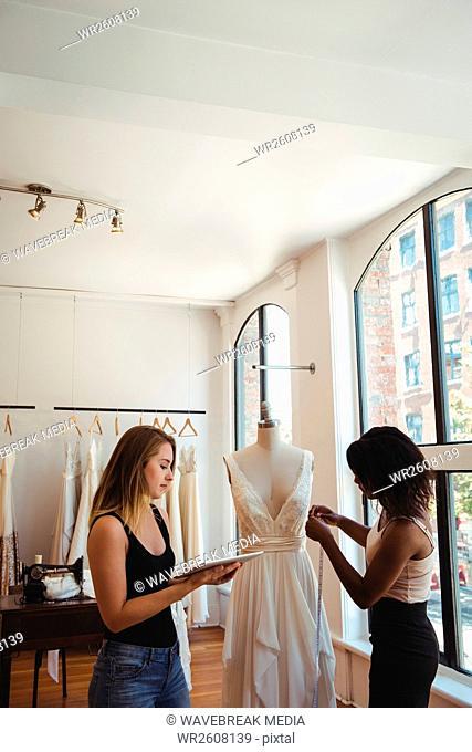 Female fashion designers working on a digital tablet