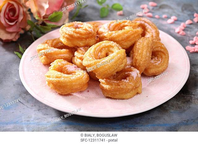 Churros with sugar on a pink plate