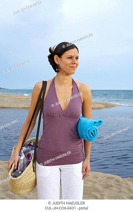 Young woman with beach bag on beach