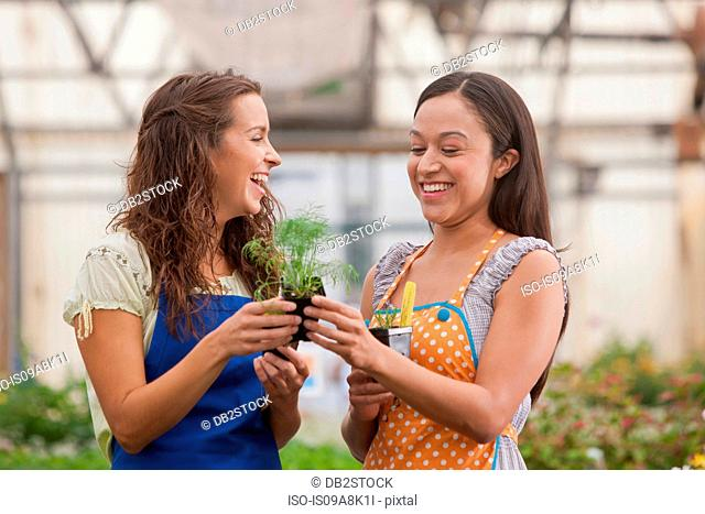 Young women holding plant in garden centre, smiling