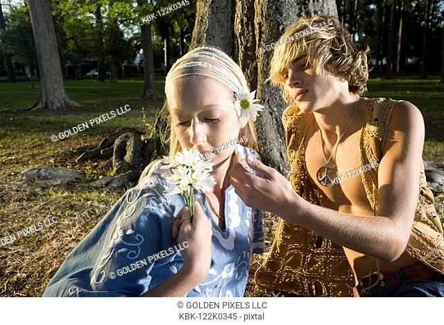 Young affectionate hippie couple relaxing under tree