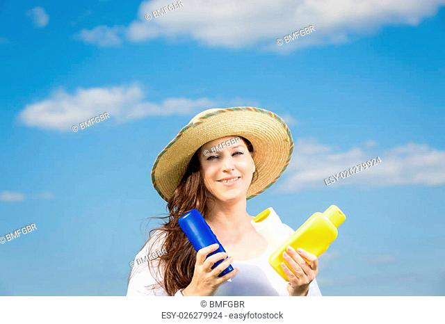 woman against blue sky holding some sun milks