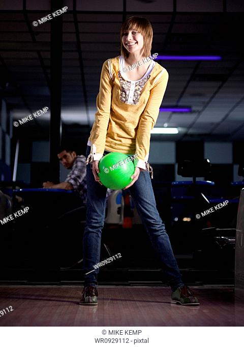 USA, Utah, American Fork, young woman holding bowling ball and smiling