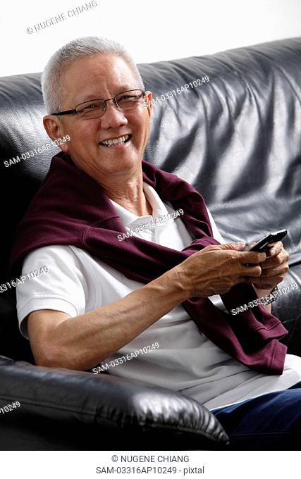 mature man with grey hair smiling holding a phone