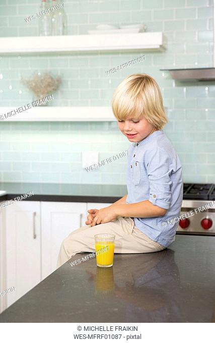 Boy in kitchen with glass of orange juice
