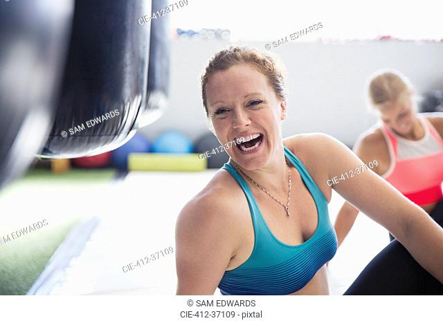 Portrait laughing female boxer stretching in gym