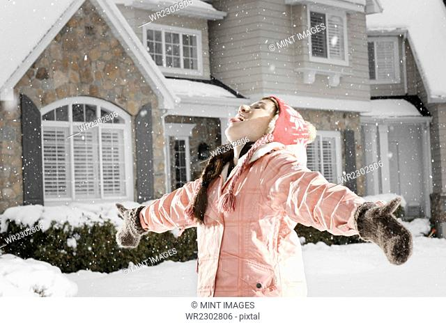 Winter snow. A girl holding out her arms with her head back, catching the falling snow in her open mouth