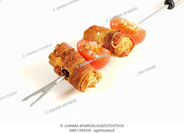 Sausage skewers with bacon and cherry tomatoes on white background