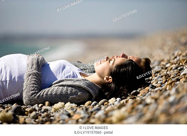 A pregnant woman and her partner lying on the beach