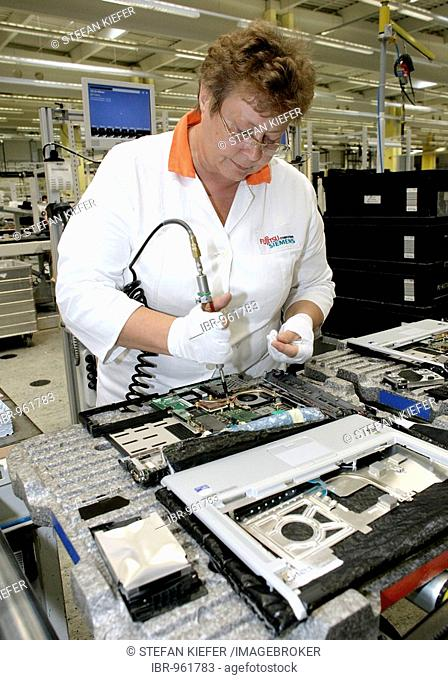 Employee of the computer production installing the mainboard into a notebook, at the Fujitsu Siemens GmbH in Augsburg, Bavaria, Germany, Europe